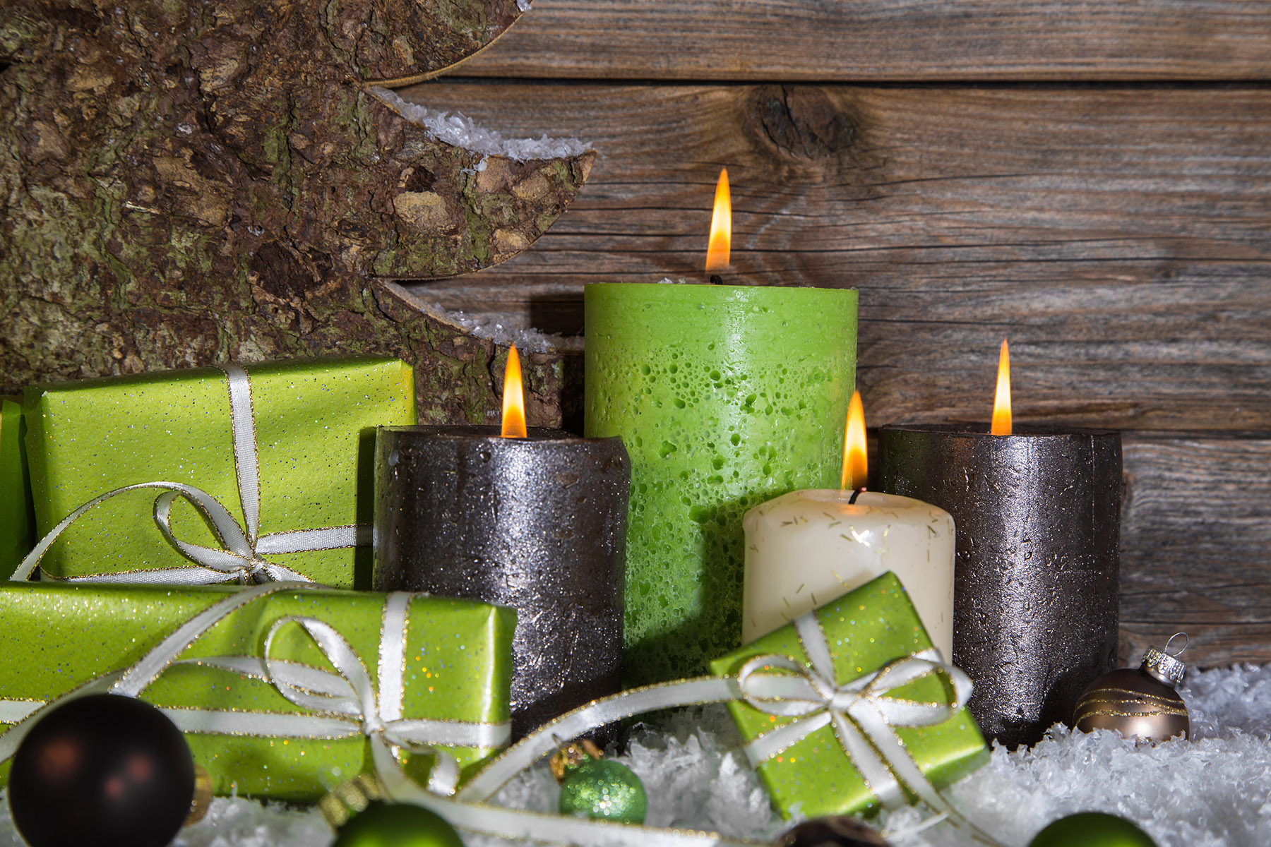 burning-holiday-candles-and-gifts-on-snowy-background
